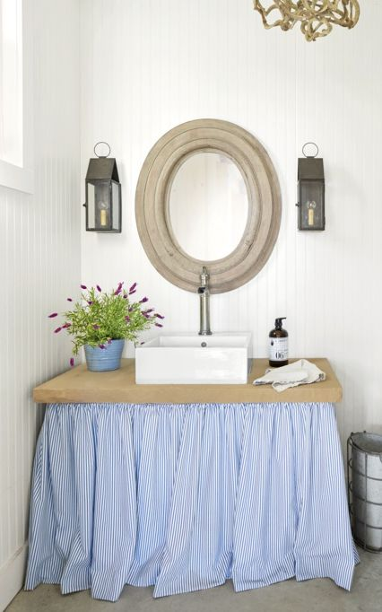 Outdoor Style Lantern in white bathroom with accessories and plant with round mirror
