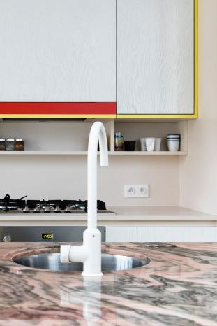 Pink Marble countertops in light kitchen with red and yellow accents