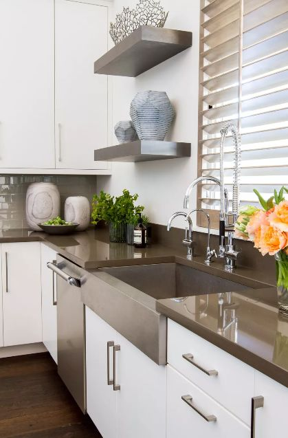 Kitchen with brown countertops and white cabinets with shelves and plants