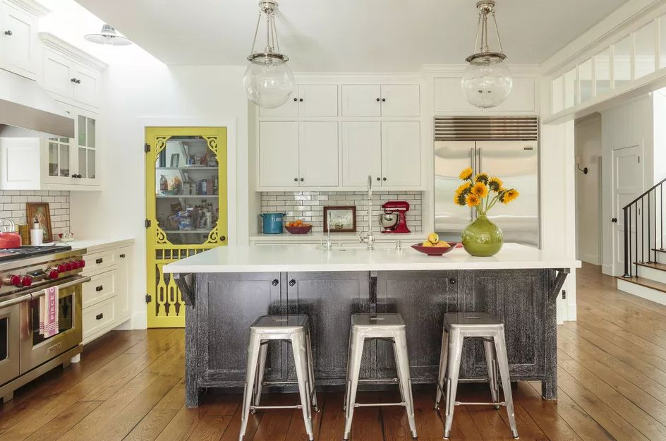 White kitchen with contrasting colors red oven knobs and yellow pantry door