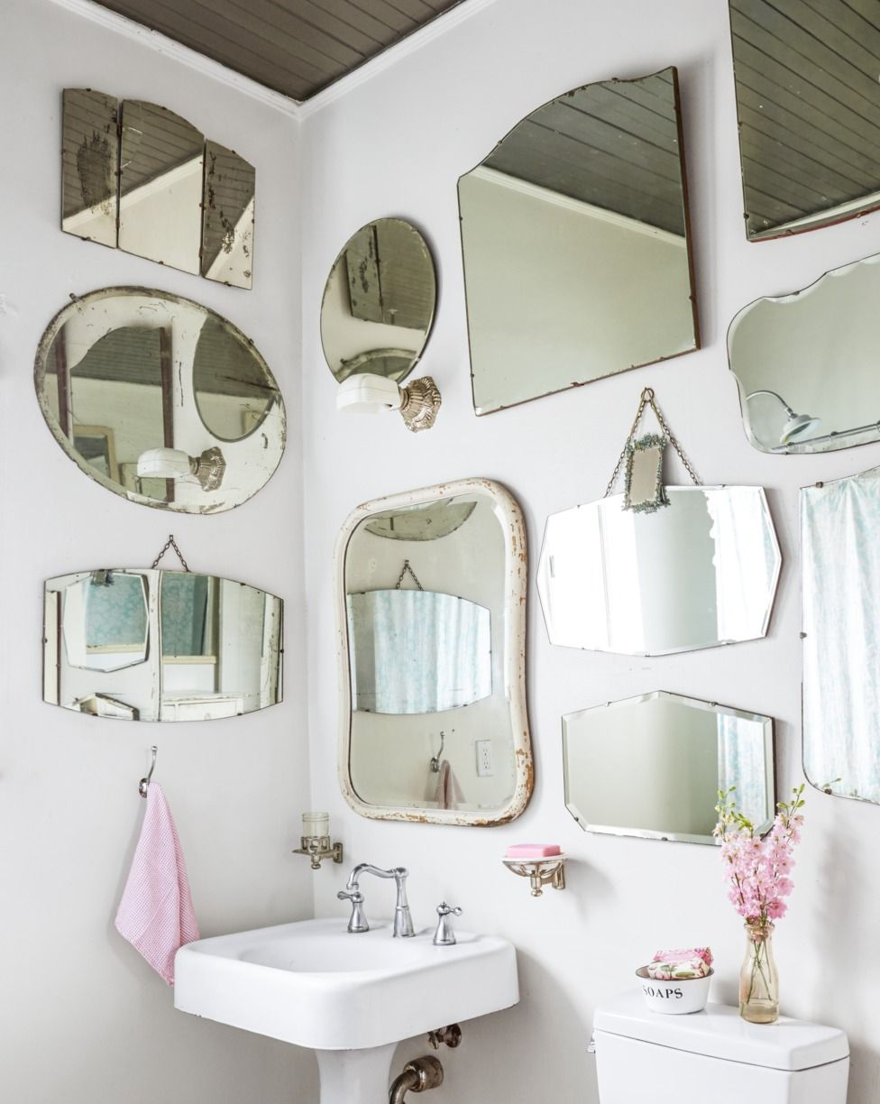 Single Vintage Sconce and rustic bathroom lighting ideas with wall of mirrors and pink accessories