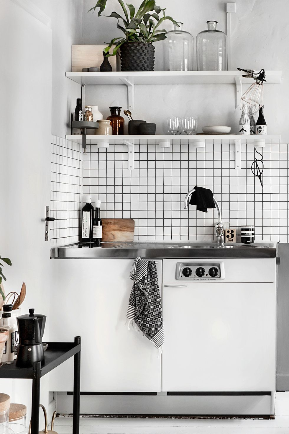 Stainless steel countertop in white kitchen with storage shelves