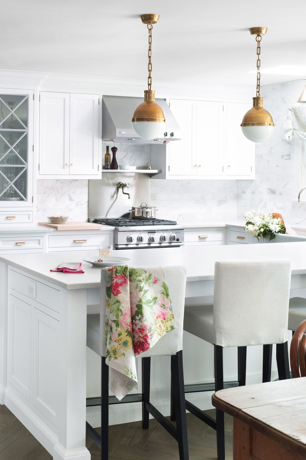 White kitchen cabinets with decor with gold lighting and floral accents