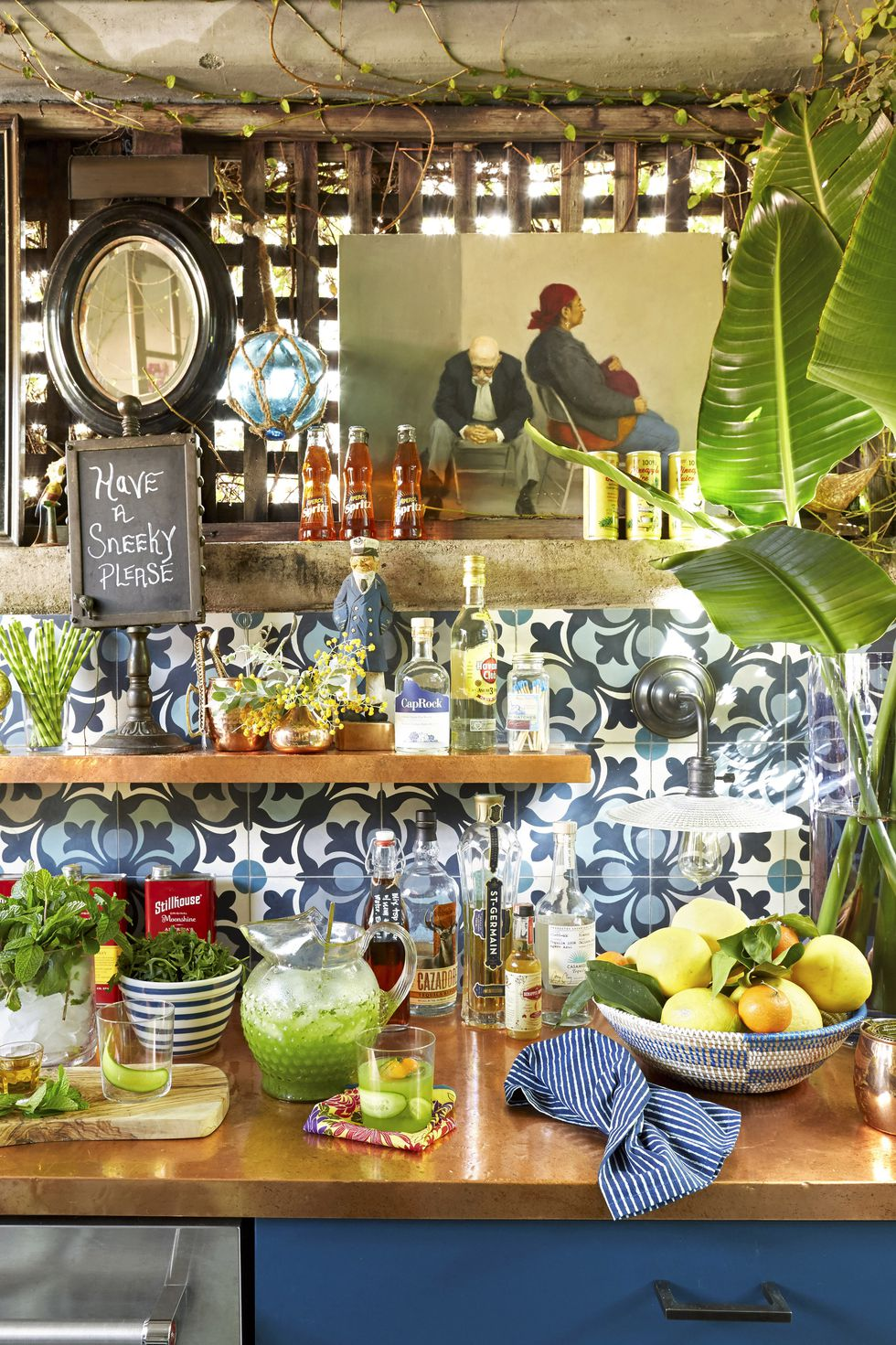 Summery kitchen with shelf, bottles including plants and artwork