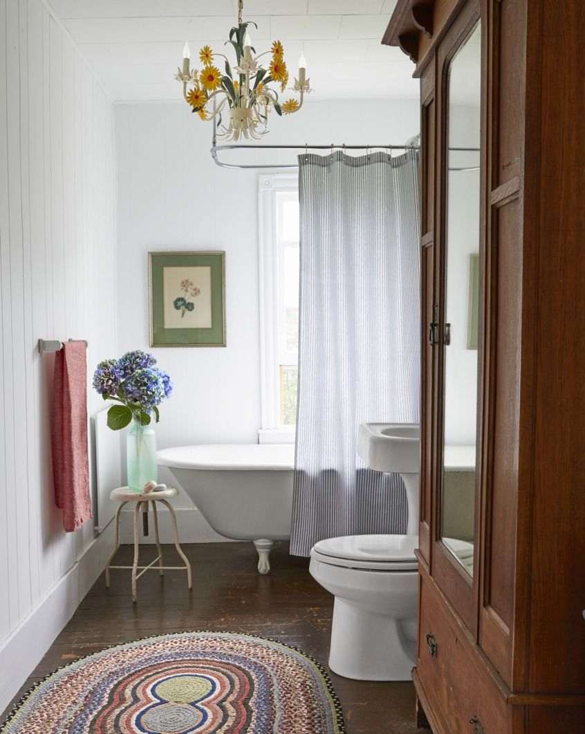 Tole Chandelier in white bathroom with large wooden storage cabinet with wood floor and artwork