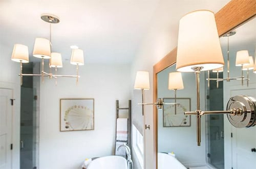 Traditional Sconces and rustic bathroom lighting ideas in white bathroom with chandelier and large mirror