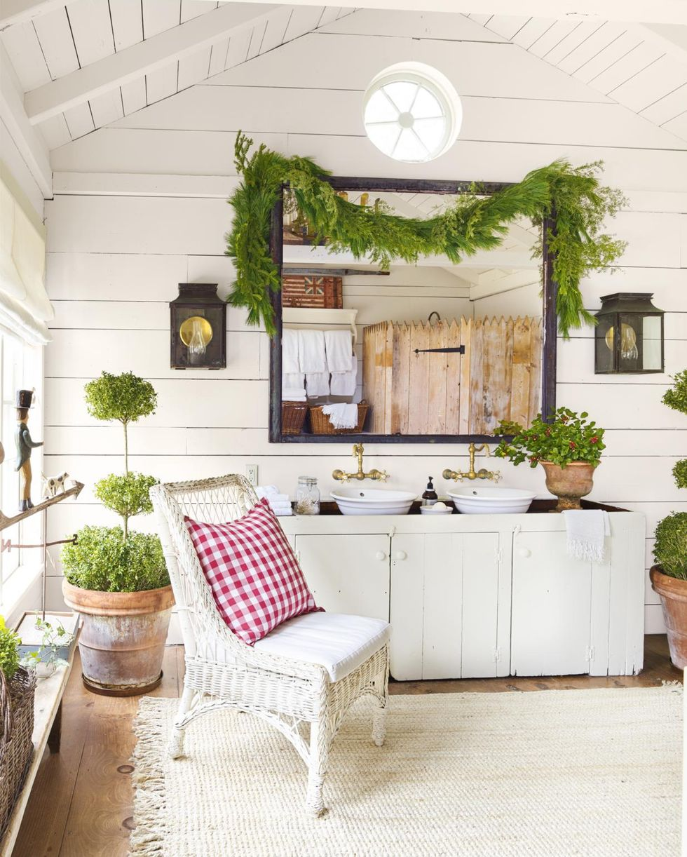 Wall Mounted Lanterns in white bathroom with chair and double sink with large square mirror with plants and other greenery