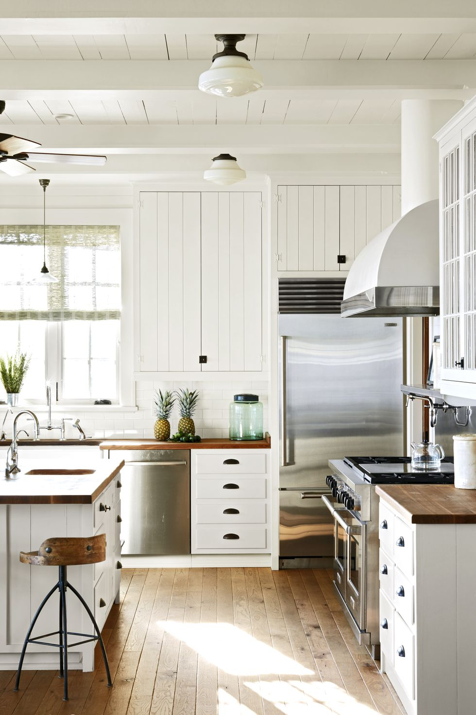 Kitchen with wood countertops and floors with white panel walls