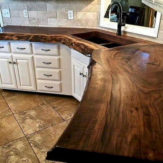Wood countertop in kitchen with white cabinets and brown tones