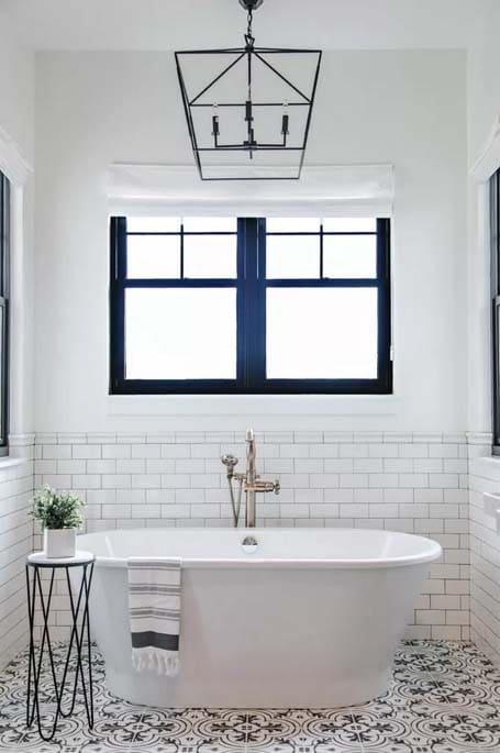 Wrought Iron Cage Chandelier with rustic bathroom lighting ideas in white bathroom with black highlights and plant