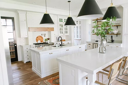 bold pendent lighting in white kitchen with black shades