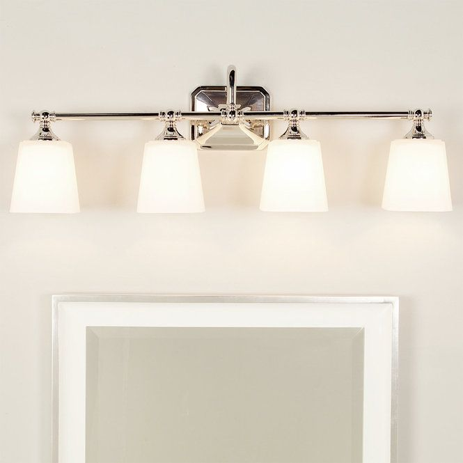 Four lights above mirror in white bathroom