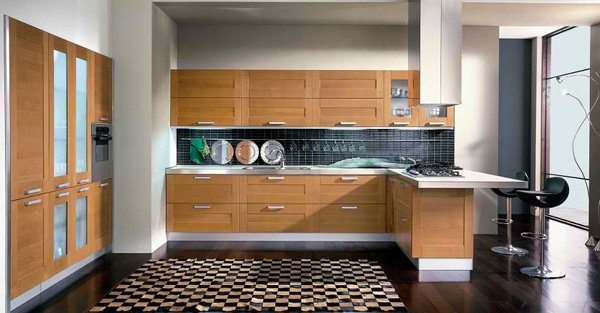 Kitchen with medium colored cabinets white walls and dark flooring
