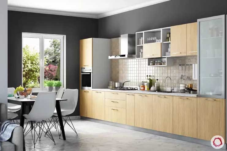 Cabinets in kitchen with large window and gray walls with black dining table