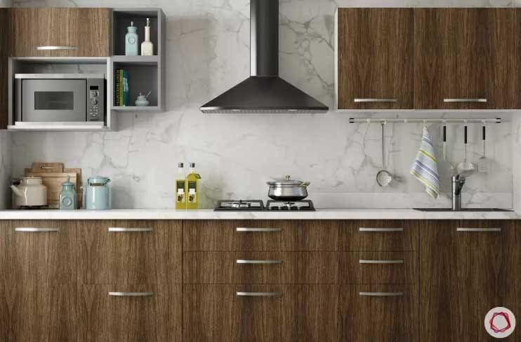 Cabinets with white marble backsplash and metal vent hood