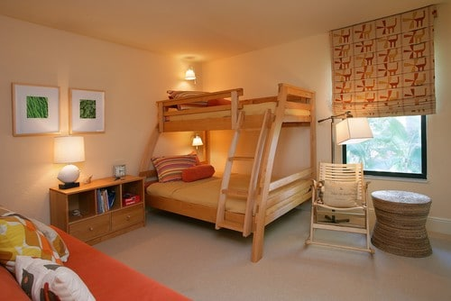 Feng shui layout with wooden bunk beds with orange couch and storage