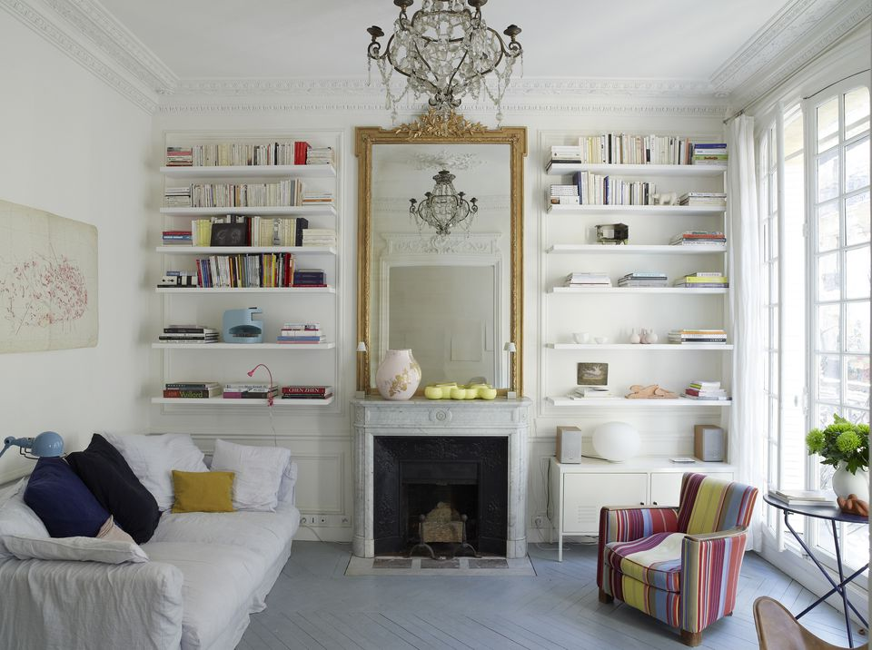 White room with large mirror and chandelier with storage book shelves