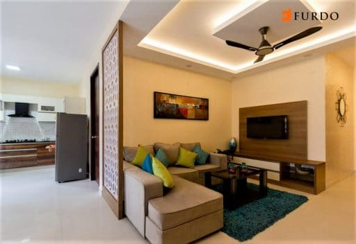 Cove lighting in room design with false ceiling and brown furniture