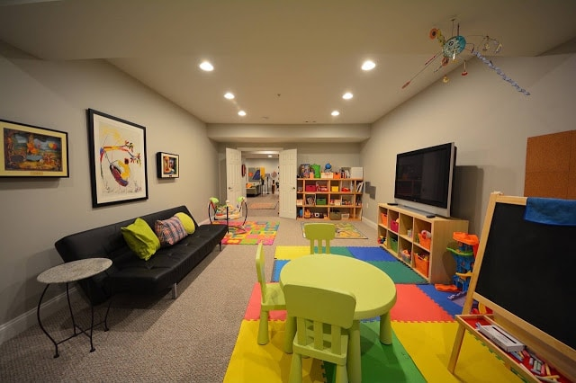 Kids playroom in basement with storage bins lots of colors and tv