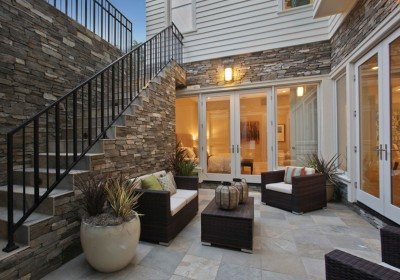 Modern Walkout Basement Ideas on display with modern outdoor furniture and stonework