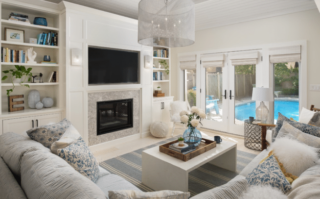 Poolside basement with bookshelves and lighter colored furniture