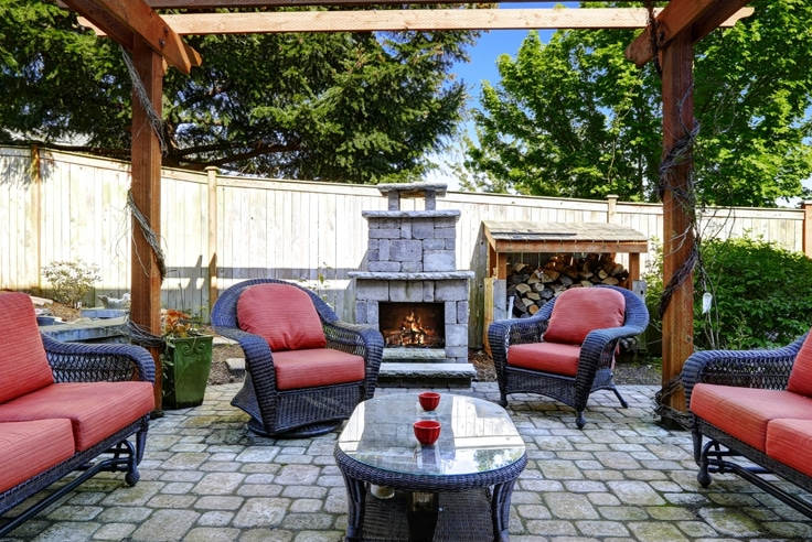 Patio with chairs pergola and wood burning outdoor fireplace