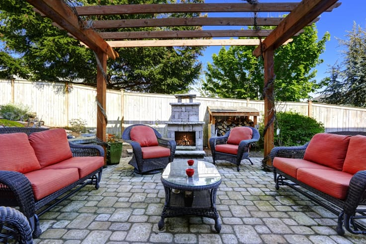 Outdoor stone patio with fireplace wooden pergola with brown and red furniture