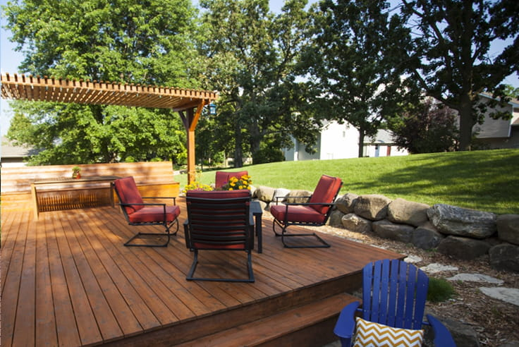 Outdoor wooden deck with red chairs and rock wall