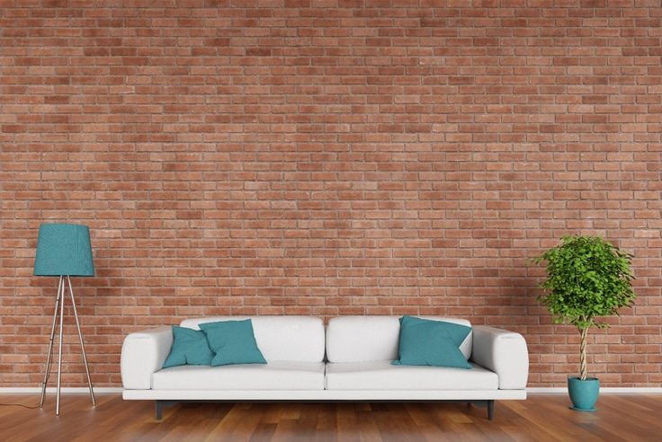 Brick wall mural idea with white couch lamp and plant
