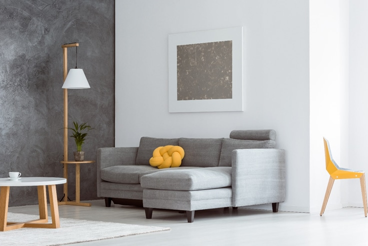 Grey accent wall with grey couch yellow pillow and white wall