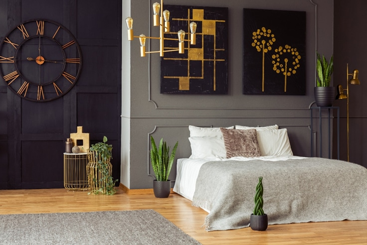 Bedroom with grey accent wall with large clock and black artwork and plants