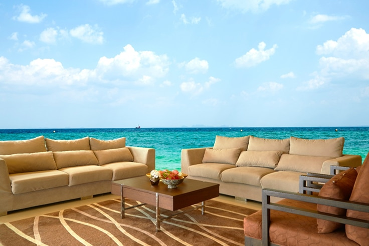 Ocean wall mural in living room with cream colored couches and coffee table