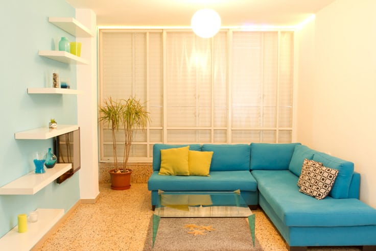 turquoise living room with yellow accent pillows and white floating shelves