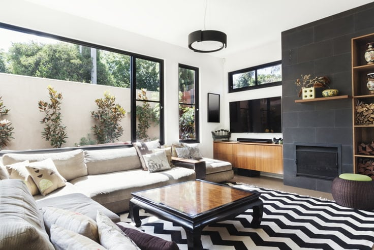 Black fireplace with large window with wood shelves and other decor