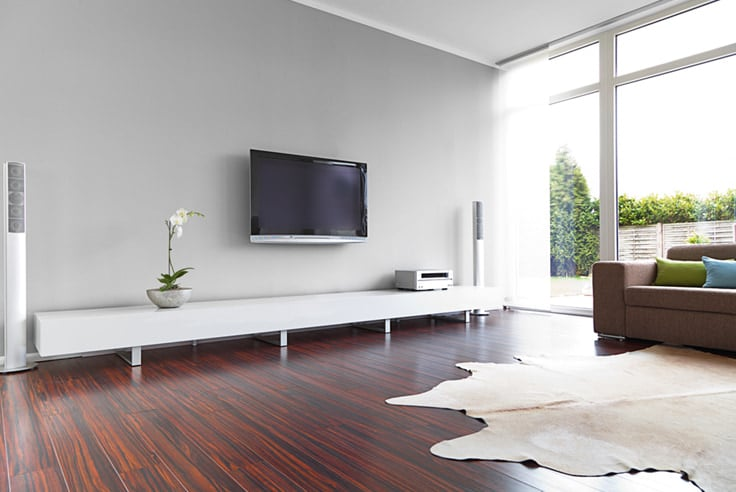 Dark floors with brown couch and white walls with tv and large window