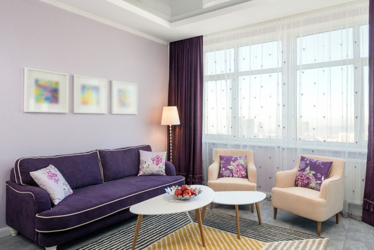 Purple couch with lavender wall art work and other light decor